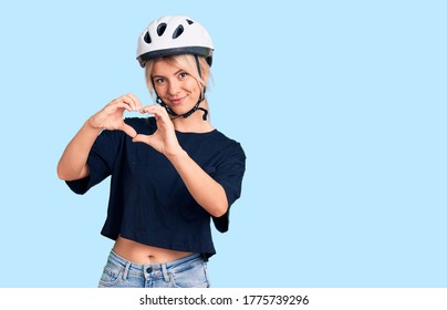 Young beautiful blonde woman wearing bike helmet smiling in love showing heart symbol and shape with hands. romantic concept.