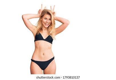 Young beautiful blonde woman wearing bikini posing funny and crazy with fingers on head as bunny ears, smiling cheerful