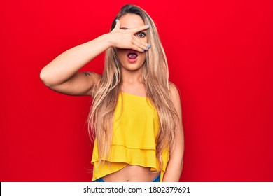 Young beautiful blonde woman wearing yellow t-shirt standing over isolated red background peeking in shock covering face and eyes with hand, looking through fingers afraid