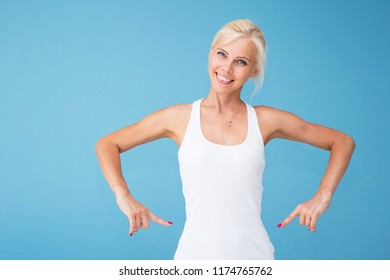 A young beautiful blonde woman in a white T-shirt is smiling and showing a slender waist, a sporty slender figure. Shooted on a clean blue background.