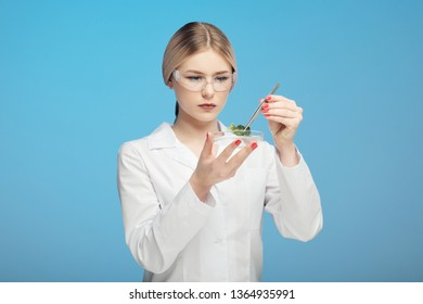 Young beautiful blonde woman in white coat and goggles, blue background. Holds tweezers and plant leaf. Concept science, study of plants. GMO test. Scientist biologist and chemist, microbiologist.