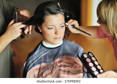 Young beautiful bride applying wedding make-up by make-up artists