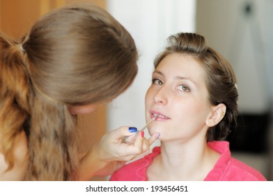 Young beautiful bride applying wedding make-up by professional make-up artist (focus on brush)