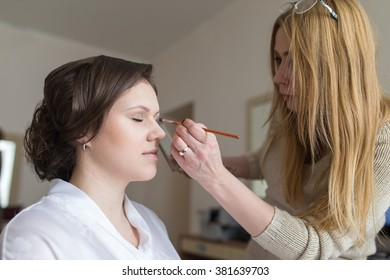 Young beautiful bride applying wedding make-up  by professional artist