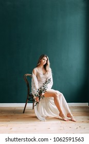 Young beautiful bride in boudoir and wedding dress, with a wreath and a bouquet in her hands. London wedding trends, stylish photoshoot
