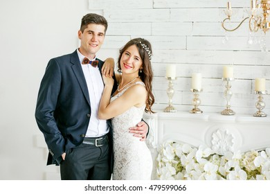 Young and beautiful bride and groom standing next to a white chimney. They hug and smile. Around a beautiful wedding decor. Portrait.