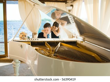 Young beautiful bride and groom at the white grand piano on a boat with a river at the background