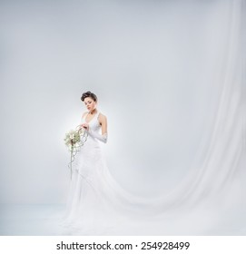 Young and beautiful bride in a long fantasy dress standing with a flower bouquet over the grey background.
