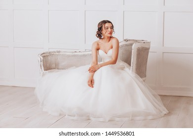 Young beautiful bride in a luxurious wedding dress sitting in a white room