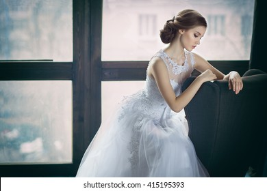 The young beautiful bride sitting beside the window