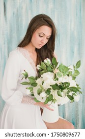 Young beautiful bride. In a white luxurious dress. With a bouquet of white flowers.