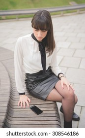Young beautiful brown hair businesswoman seated on a bench in a city park using a smartphone looking downward the screen - business, technology, communication concept