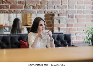 A young beautiful brown-haired girl in a white shirt is sitting at a table in a cafe by the window opposite a brick wall, drinking cappuccino coffee and dessert with whipped cream. Breakfast and lunch