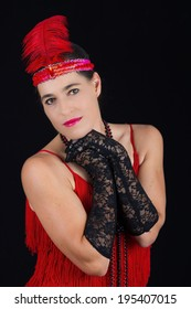 Young beautiful brunette in 1920 style attire red dress and feather