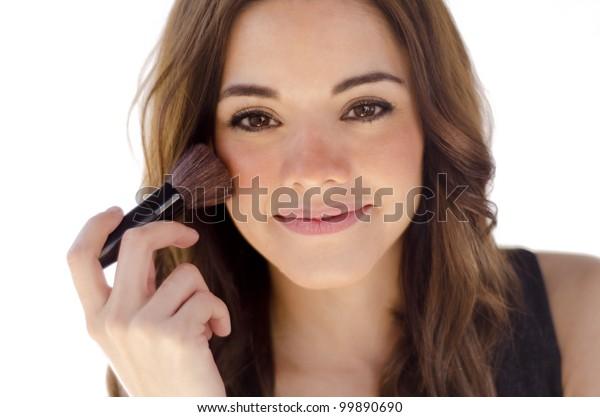 Young beautiful brunette applying blush