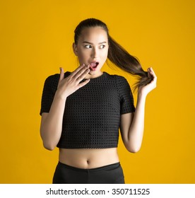 young beautiful brunette Asian girl in a studio on a yellow background in shirt surprise laughs and covers her mouth