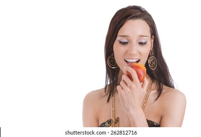 Young beautiful brunette bites off red apple.