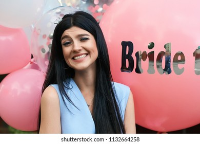 Young beautiful brunette bride to be with black hair and silver crown smiling on bachelorette party balloon background