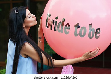 Young beautiful brunette bride to be with black hair and silver crown on it kissing her pink bachelorette party balloon