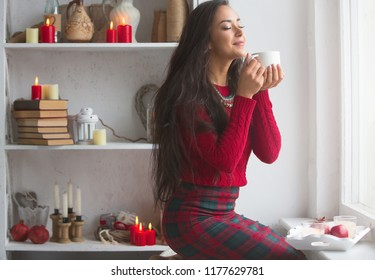 Young beautiful brunette in a bright red sweater and plaid skirt. A girl drinks a hot drink by the window. Warm comfortable room with lots of decor