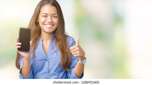 Young beautiful brunette business woman showing screen of smartphone over isolated background happy with big smile doing ok sign, thumb up with fingers, excellent sign