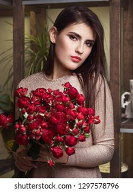 Young beautiful brunette business woman florist holding trendy bouquet of peony roses in flower shop