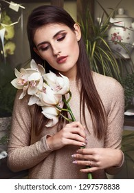 Young beautiful brunette business woman florist holding orchid branch of fresh flowers in flower shop