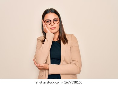 Young beautiful brunette businesswoman wearing jacket and glasses over white background thinking looking tired and bored with depression problems with crossed arms.
