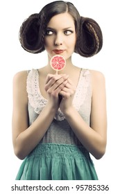 young beautiful brunette with a creative luxury hair style and a colored lollipop. She is in front of the camera, looks at right and takes the lollipop near the mouth