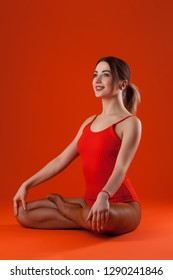 young beautiful brunette dancer woman in orange swimsuit posing on isolated red studio background