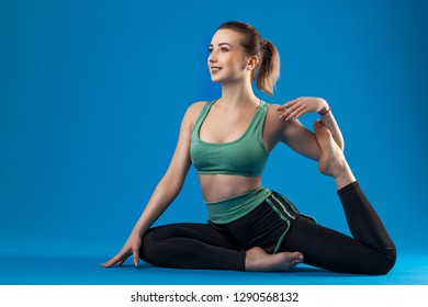 young beautiful brunette dancer woman posing on isolated blue studio background