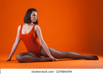 young beautiful brunette dancer woman posing on isolated studio background