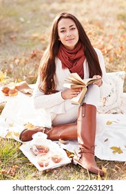 young beautiful brunette drink tea and read book in the autumn park