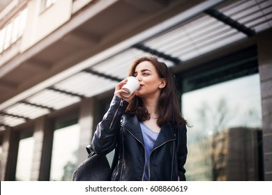 young beautiful brunette drinking coffee walking around the city.leather jacket,urban backpack , bright red lips Posing against the window of the boutique Model looking aside and drinking coffee