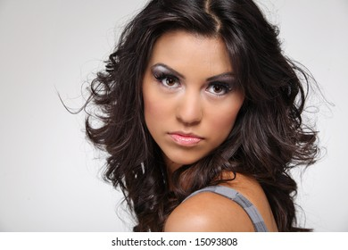 Young beautiful brunette fashion model in blue dress on white background.