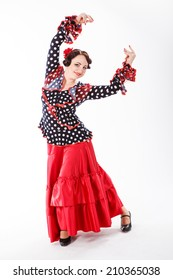 young beautiful brunette female spanish flamenco dancer in black shirt and red flamenco skirt posing with red fan in her arms in studio on gray background