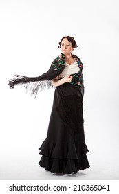 young beautiful brunette female spanish flamenco dancer in white shirt and black flamenco skirt dancing with black flower shawl in her arms in studio on gray background