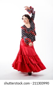 young beautiful brunette female spanish flamenco dancer in black shirt and red flamenco skirt dancing with her arms in studio on gray background