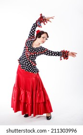 young beautiful brunette female spanish flamenco dancer in black shirt and red flamenco skirt dancing with fan red in her arms in studio on gray background