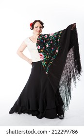 young beautiful brunette female spanish flamenco dancer in white shirt and black flamenco skirt posing with black flower shawl in her arms in studio on gray background