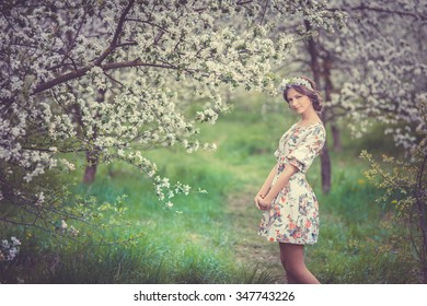 Young beautiful brunette girl in blooming garden