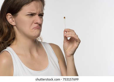 Young beautiful brunette girl cleans the ears with white chopsticks with cotton wool and is surprised to get a lot of yellow earwax