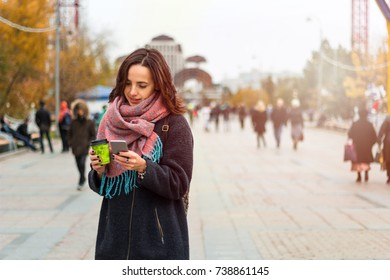 young beautiful brunette girl with  coffee to go  and smartphone on the background of blurred city  street