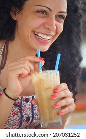 Young beautiful brunette girl drinking iced coffee and having fun.