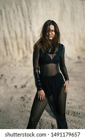 A young beautiful brunette girl in fashionable black clothes poses in sand quarry on sunny summer day. Sandpit. Transparent dress. Fashion concept. Wind disperses the hair. She looks at the camera.