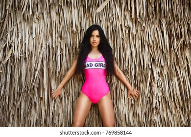 Young beautiful brunette girl in front of the huts made of palm leaves on the beach of a tropical island. Summer vacation concept.