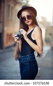 young beautiful brunette girl in a hat, sunglasses, t-shirt and jeans with a film camera in hand walks along the ancient city