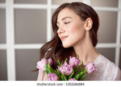 Young beautiful brunette girl holding spring bouquet of tulips in her hands