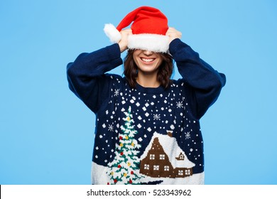 Young beautiful brunette girl in knited sweater and christmas hat smiling  over blue background.