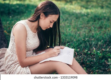 A young beautiful brunette girl with long hair in a summer dress sits on a lawn near a tree and writes a letter to her beloved man. Letter to a soldier. Romance writing a letter.